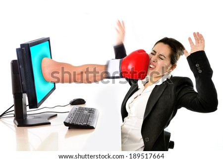 business woman sitting on desk with with computer hit by boxing glove coming out of monitor in social media network , mobbing, bullying, cybermobbing , cyberbullying  and stress at work concept - stock photo