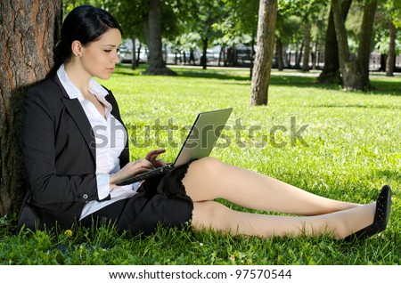 Business woman sitting on green grass and working on laptop in the park
