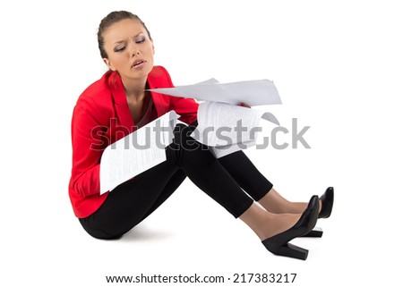 Business woman sitting on the floor with a pile of papers