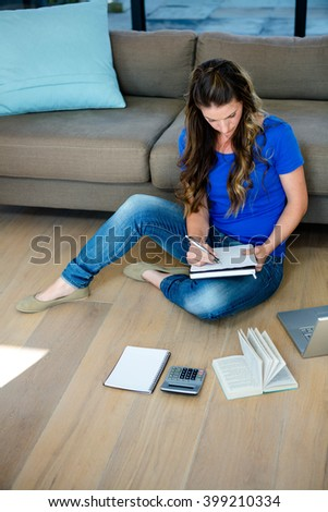 business woman sitting on the floor writing, surrounded by files - stock photo