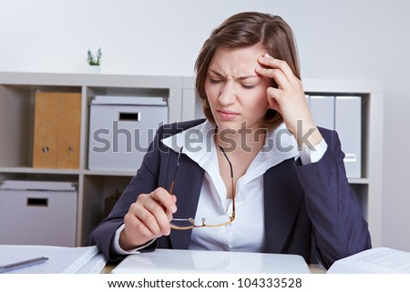 Business woman sitting with headache at her desk in the office - stock photo