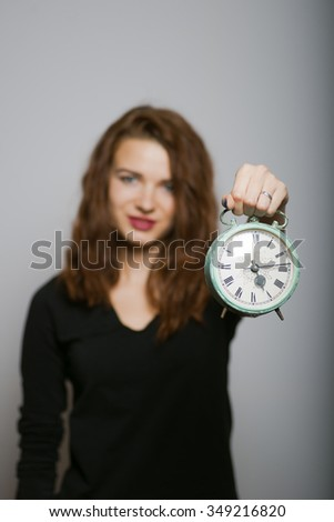Business woman slender shows a  alarm clock, studio shot isolated on the gray background