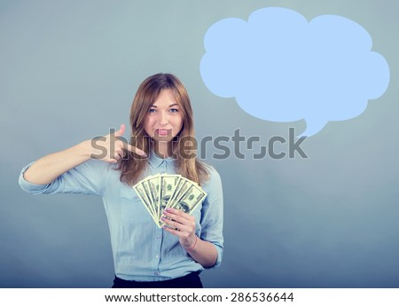 Business woman smiling and pointing finger to money on grey blue background. Woman pointing at USA notes. Young woman holds the money US dollars. Place for advertisement message. To receive a income. - stock photo