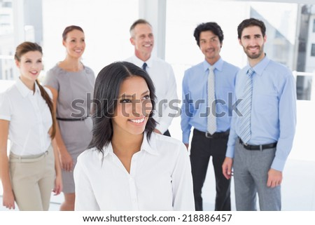 Business woman smiling at camera with co-workers behind her