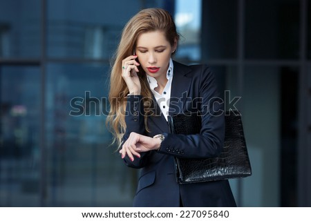 business woman speaks by phone and looks at her watch - stock photo