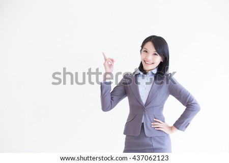 business woman stand and show something with white wall background, great for your design or text, asian
