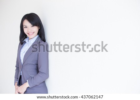 business woman stand with white wall background, great for your design or text, asian