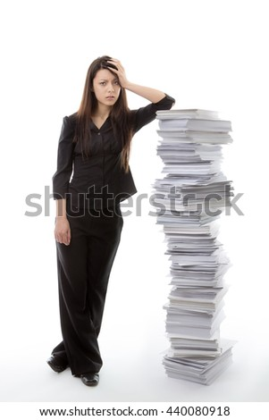 business woman standing against a large pile of paper work not looking very happy - stock photo