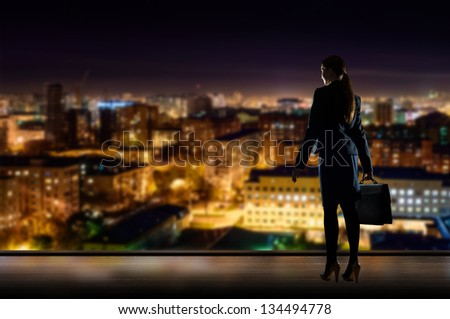 Business woman standing at the window in the night office, through the window illuminated city - stock photo