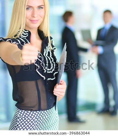 Business woman standing in foreground , showing ok - stock photo