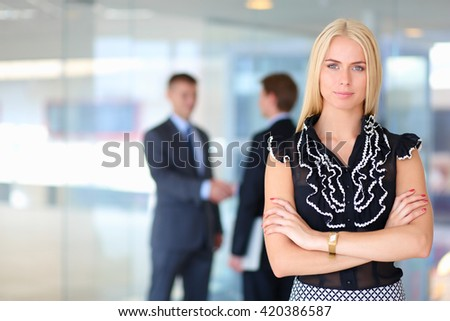 Business woman standing in foreground with a folder in her hands