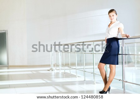 Business woman standing in the lobby of the office, based on the railing of the balcony - stock photo