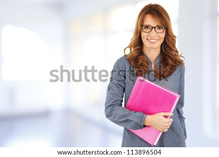 Business woman standing in the office, holding a file in her hands - stock photo