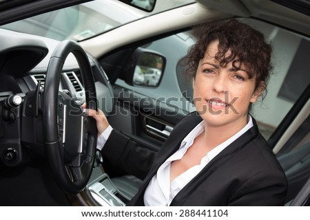 Business woman standing next to his car