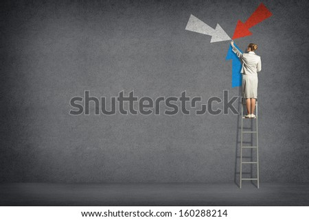 business woman standing on a ladder and touches the symbol of the arrows on the wall