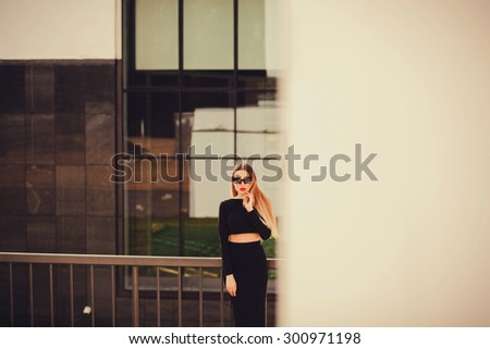business woman standing outdoors. office buildings. looking at the camera