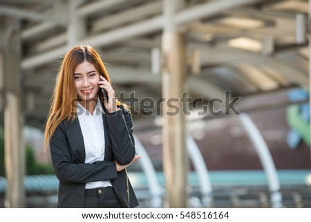 Business woman standing talking with mobile phone in city