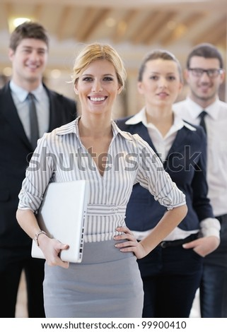 business woman standing with her staff in background at modern bright office conference room - stock photo