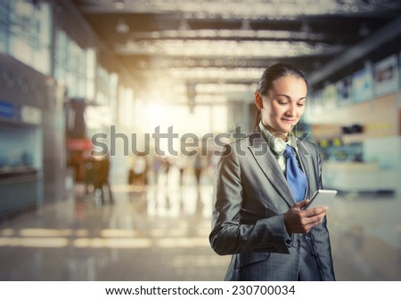 Business woman stands looking at her phone - stock photo