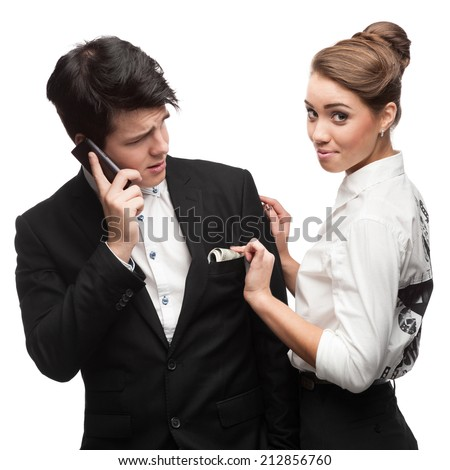 business woman stealing money from businessman pocket while he talking on cell phone