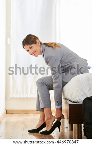 Business woman taking off her shoes in a hotel room