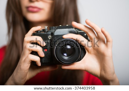 Business woman taking pictures on the retro camera, wearing glasses isolated on a gray background