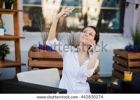 Business woman taking selfie with orange fresh juice at outdoors cafe during the lunch while waiting for her meal