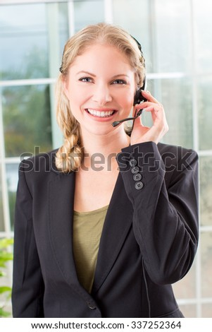 Business woman talking on a head set in her office - stock photo