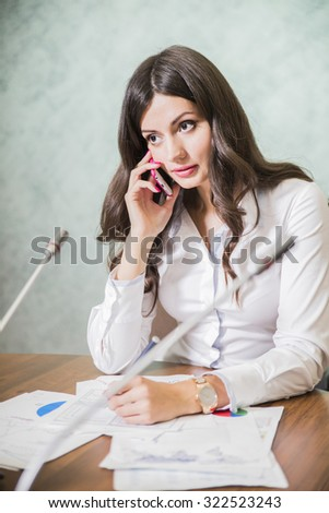 business woman talking on phone sitting at table in office