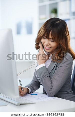 Business woman talking on telephone and making marks on the chart