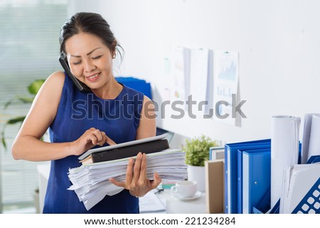 Business woman talking on the phone and using digital tablet - stock photo