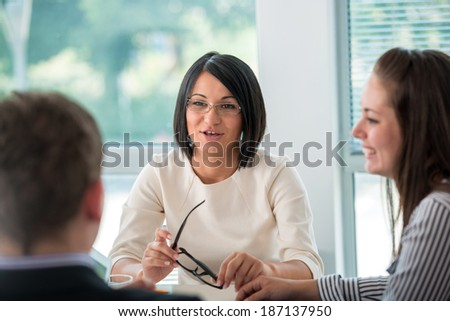 Business woman talking to a team of coworkers in meeting