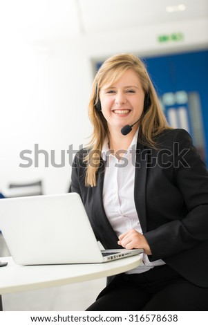 Business woman talking using her headset in the office