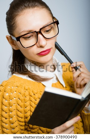 business woman thinking over notes in a notebook, hipster glasses isolated on a gray background - stock photo