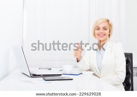 Business woman thumb up gesture, smile business woman sitting at modern white office desk - stock photo