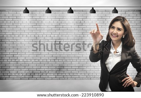 Business Woman touching an imaginary screen with her finger. on brick wall background with copy space for your design. - stock photo