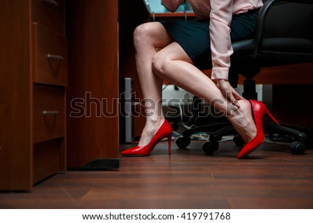 Business woman touching feet with her hand. - stock photo