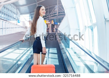 business woman traveling in airport with a bag on moving travelator - stock photo
