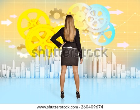 Business woman turned back looking at colorful office skyscrapers. - stock photo