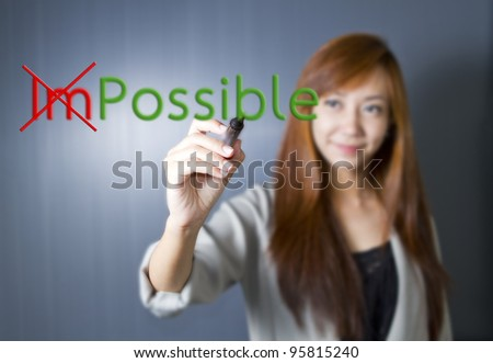 "Business woman turning the word ""Impossible"" into ""Possible"""