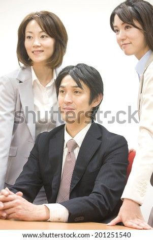 Business woman two people standing on both sides of the business man sitting in a chair