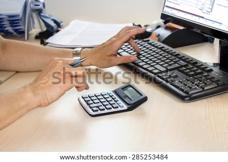 Business woman typing on calculator in the office