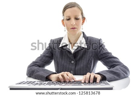 Business woman typing on keyboard at white office desk.