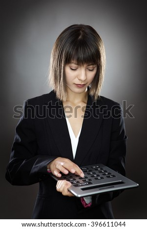 business woman using a large calculator - stock photo
