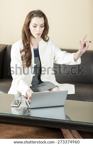 Business woman using her laptop and holding her hand up to call someone