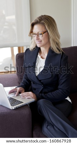 Business woman using her laptop at home - stock photo