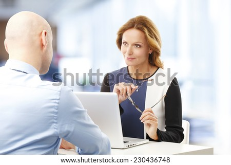Business woman using laptop and giving advise to her client. - stock photo
