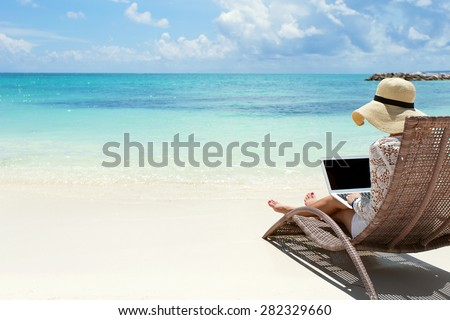 Business woman using laptop computer on the beach - stock photo