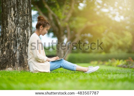 Business woman using laptop on break in city park, Young professional business woman sitting at Under a tree in the city park, Business woman working in the garden and take a rest.