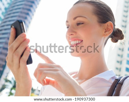 Business woman using mobile smart phone - Happy smiling business woman using mobile smart phone outdoors. - stock photo